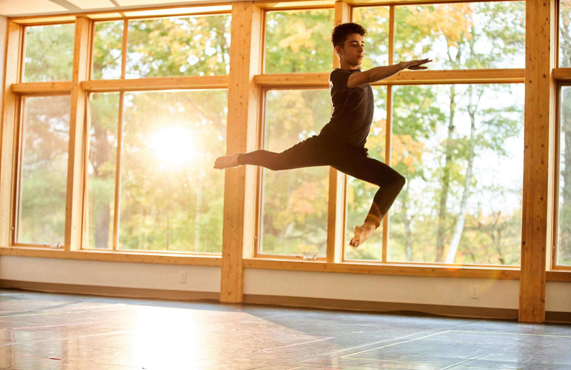 A student leaping in the dance studio.