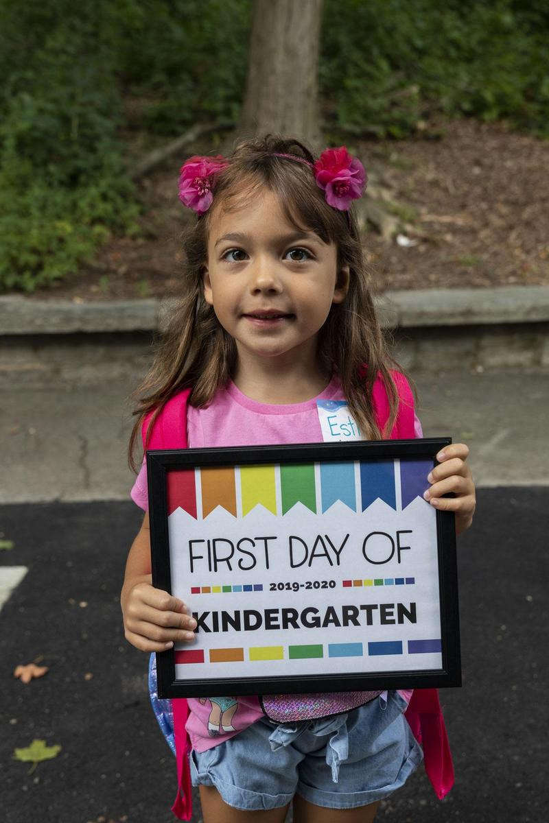 "Girl holding a sign saying ""First Day of Kindergarten"""