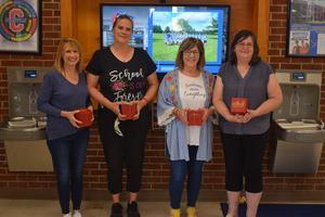 Cathy Pohlman, Monica Sottoriva, Joann Patton & Andrea Card holding a red box.