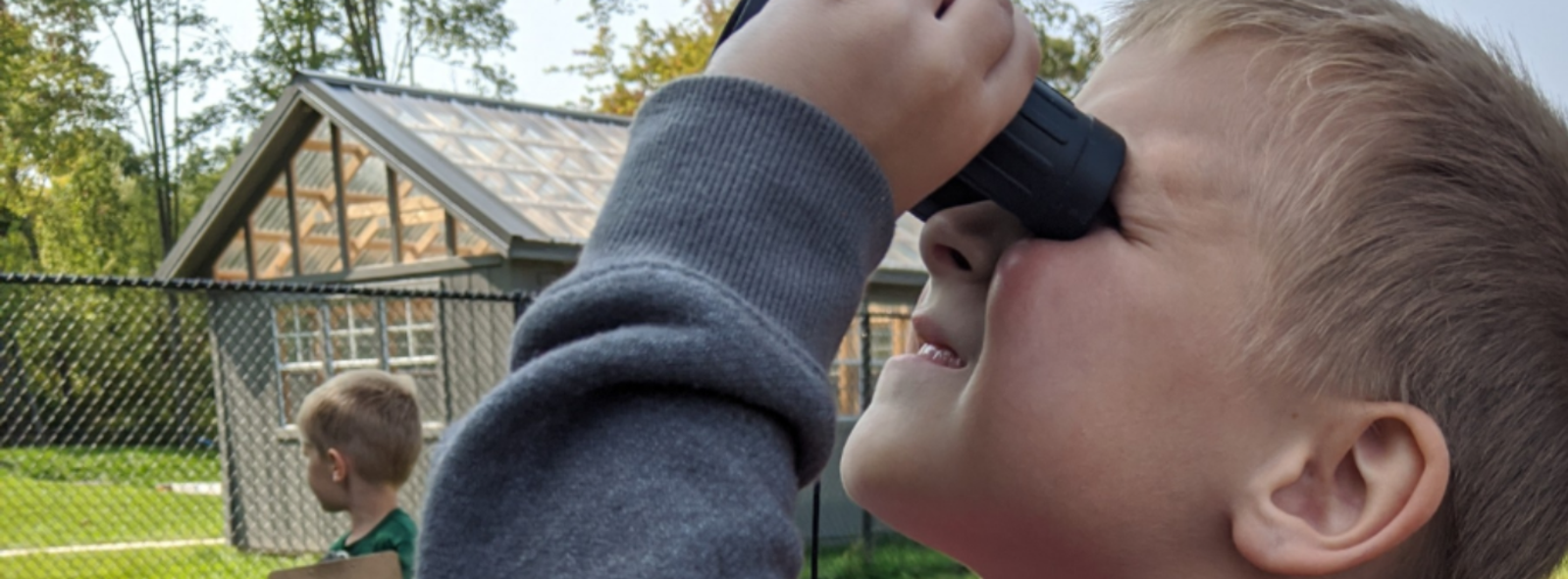 student looking up with binoculars