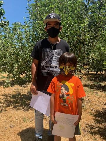 8th grade and kinder student standing in front of tree