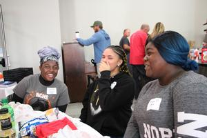 three girls smiling eating lunch