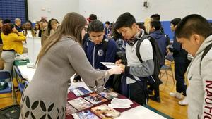 UCHS College Fair representative giving information to students