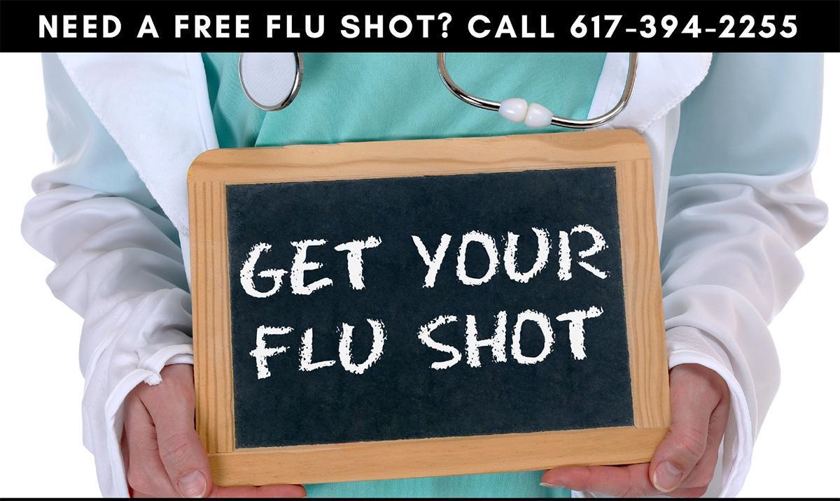 Doctor holding a flu shot sign on a chalkboard