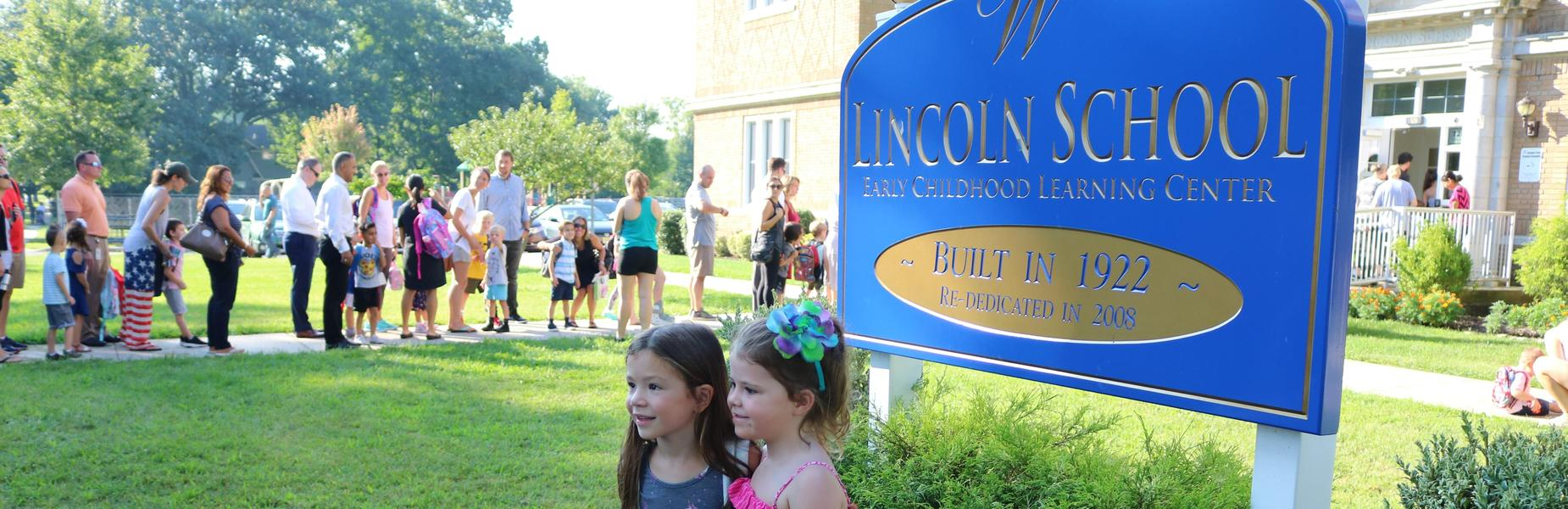 Kindergartners pose for a picture in front of Lincoln School sign on first day of school.