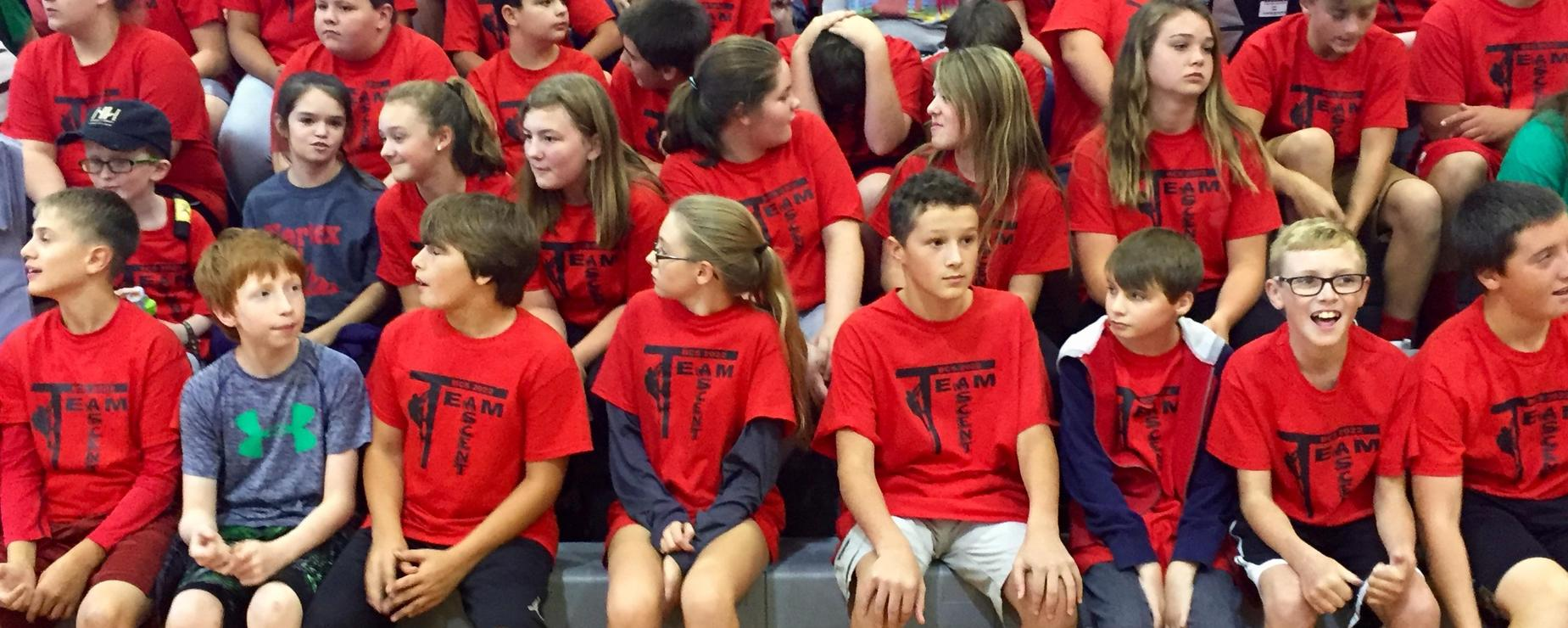 Seventh graders matching in their Team Ascent tee-shirts, waiting for an assembly