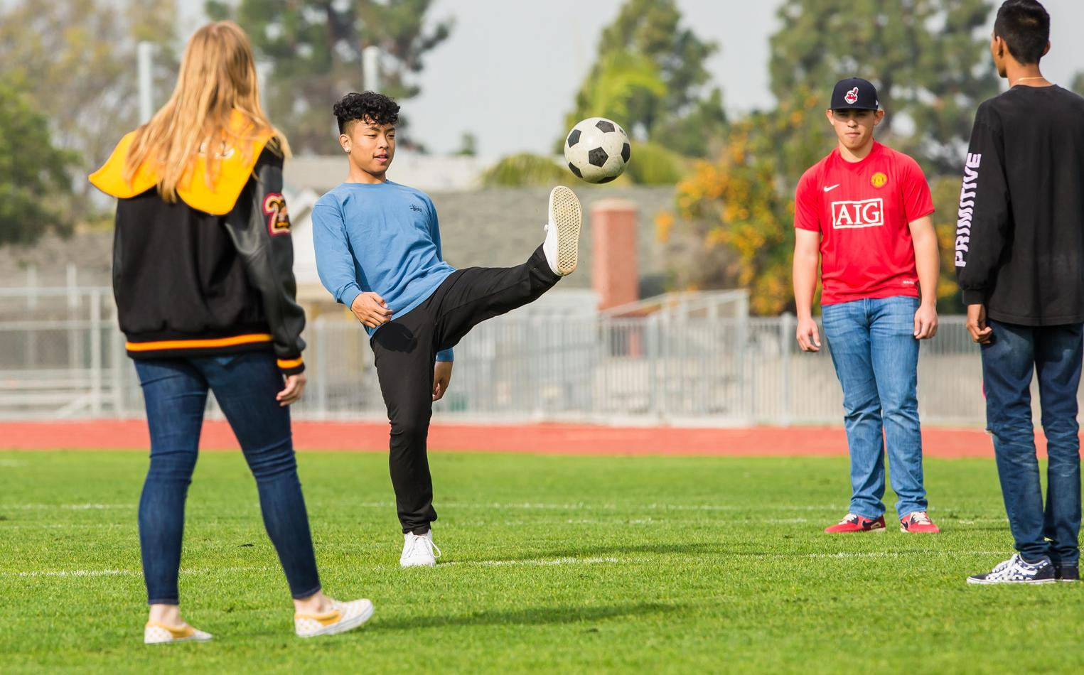 High school students on soccer field kicking around ball.
