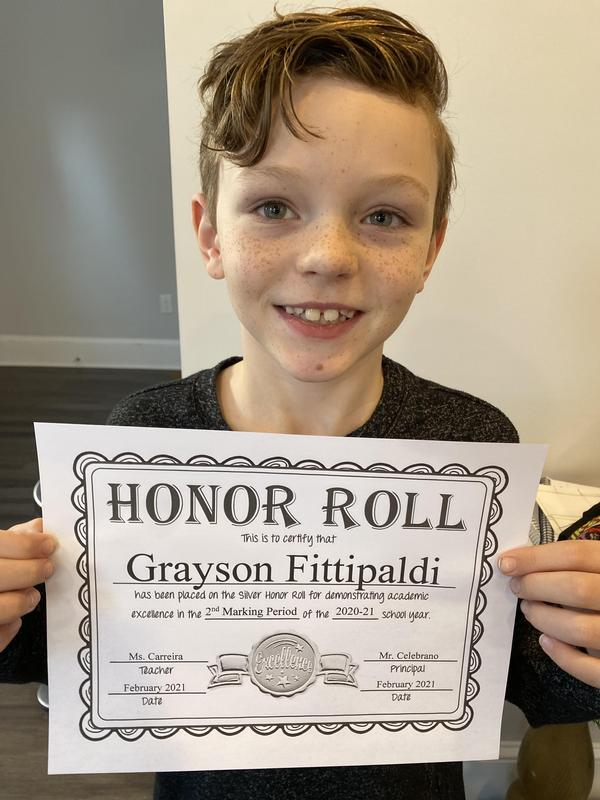 Grayson holding honor roll certificate