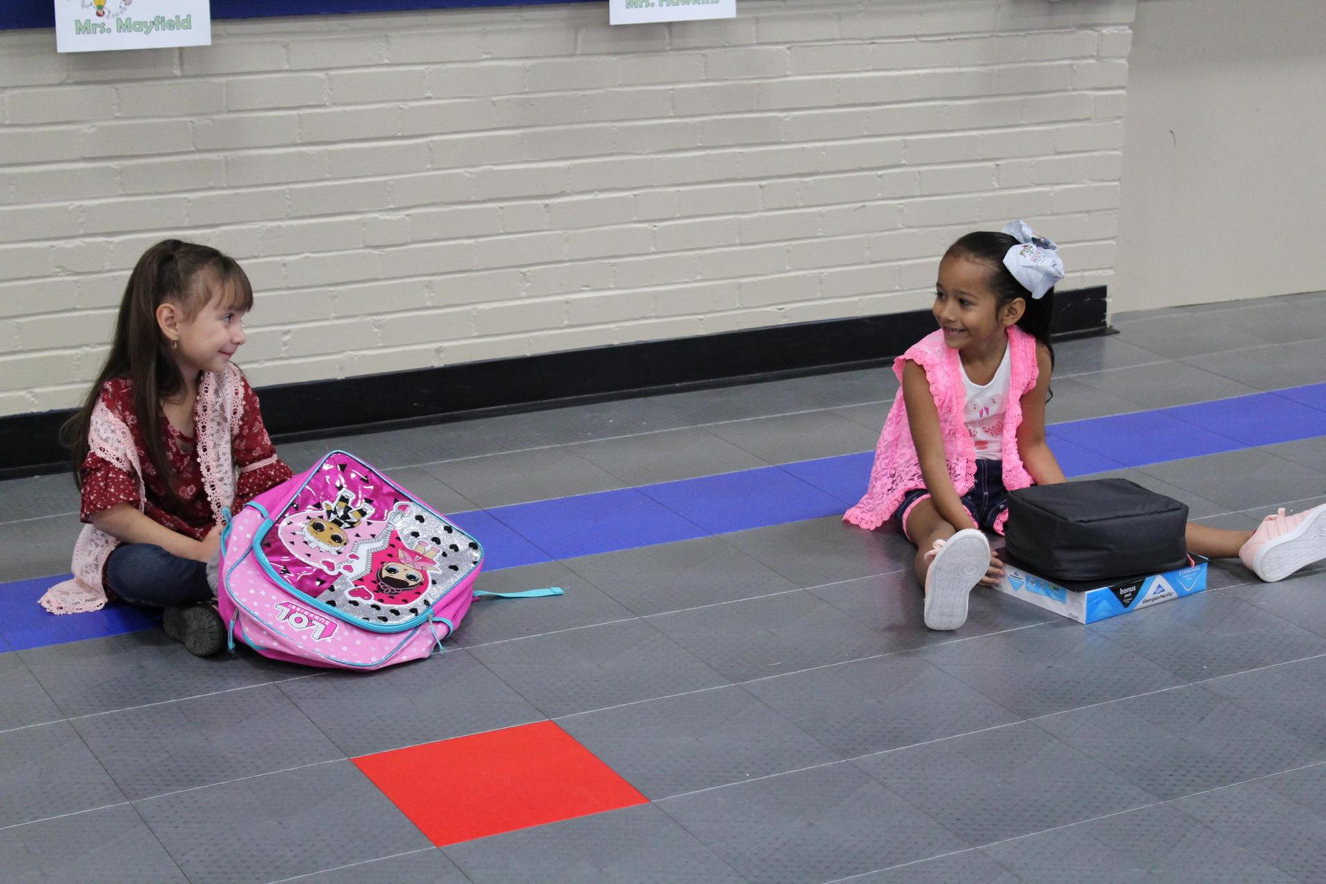 two students talking before school in the gym
