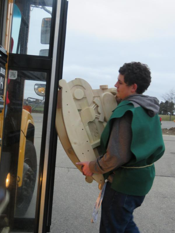 A student loads one of the toys on the bus.