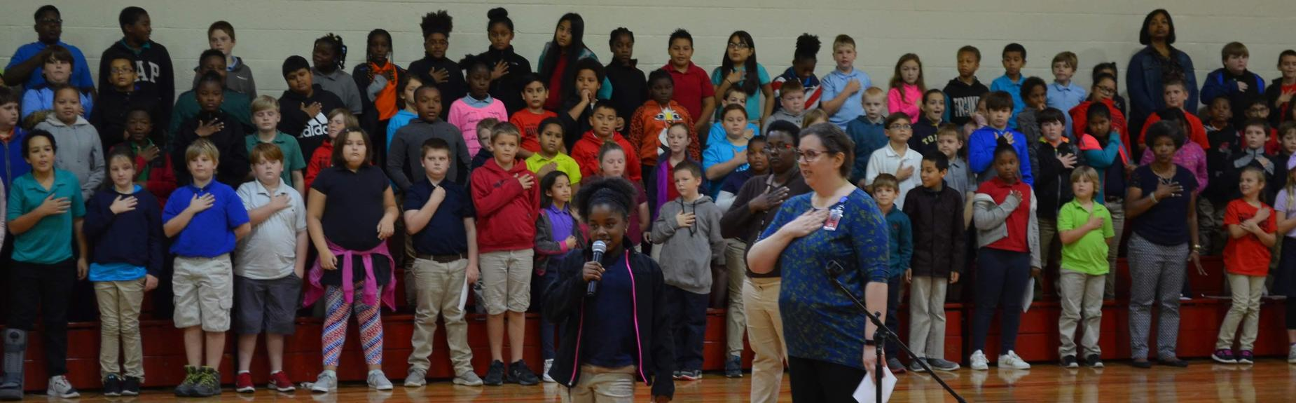 students in gym saying the Pledge of Allegiance