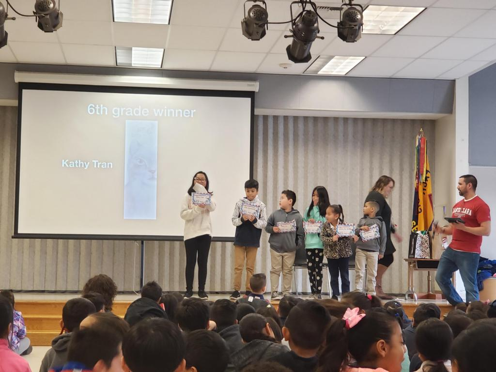 winners of bookmark contest stand on stage to accept their award