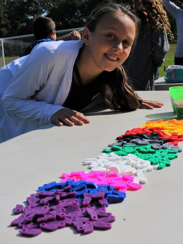 5th grade organizer of the Mileage Club at Tamaques poses next to a cup full of colorful plastic charms.