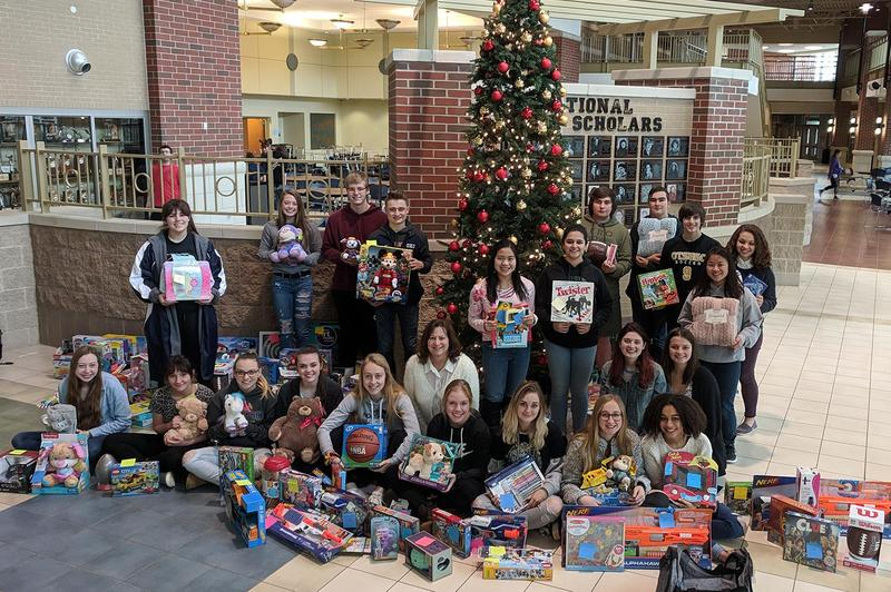 NHS members around the tree with the gifts.