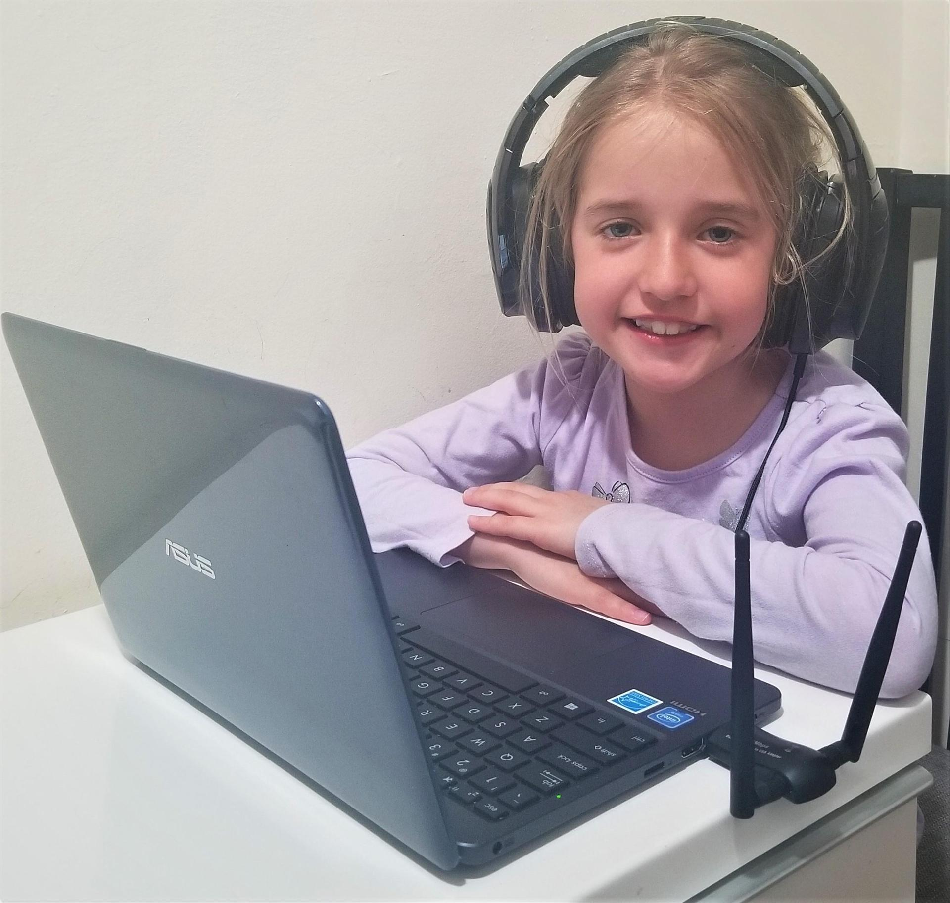 Student at home during remote learning. She is wearing headphones and looking at her laptop.