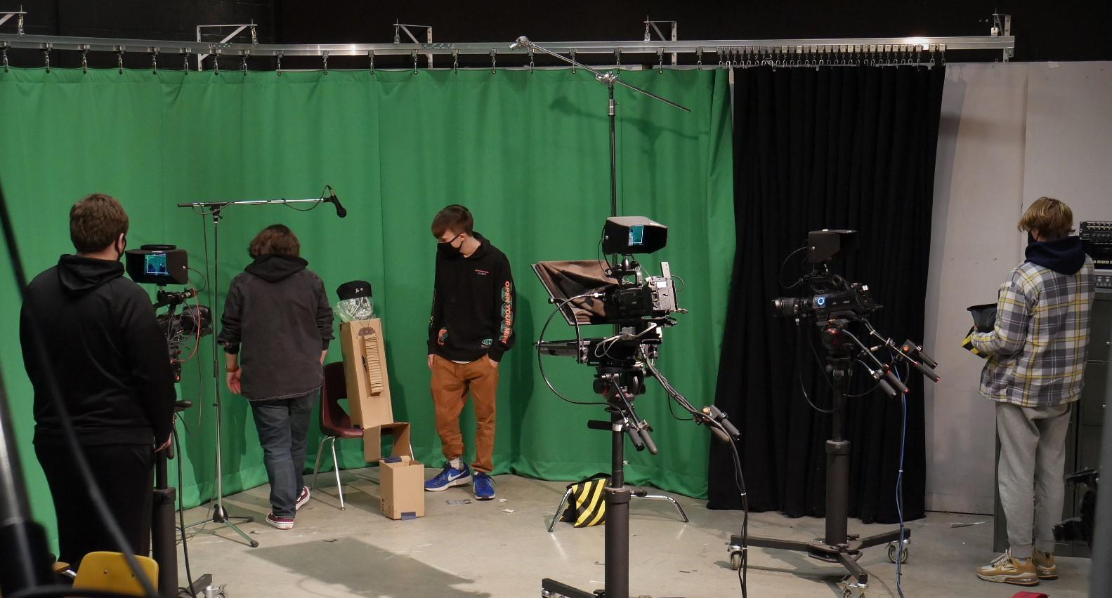 masked students working on green screen filming