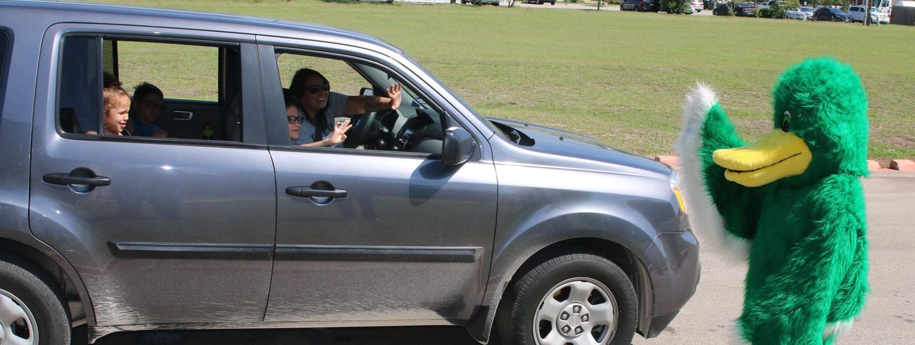 Mascot waving at children in car.