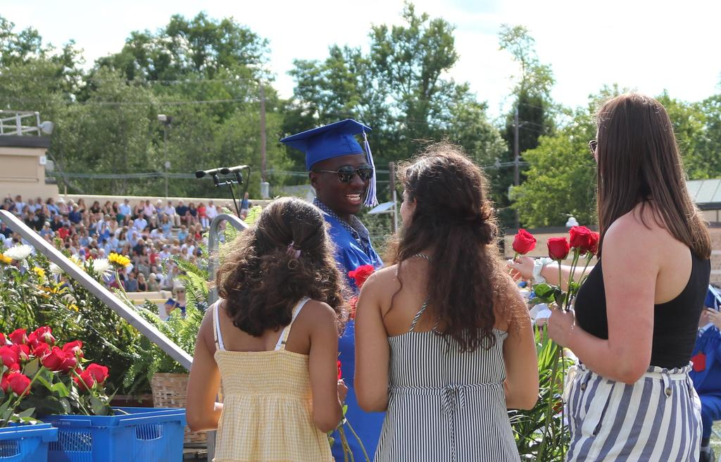Photo of smiling graduate receiving a rose after receiving diploma