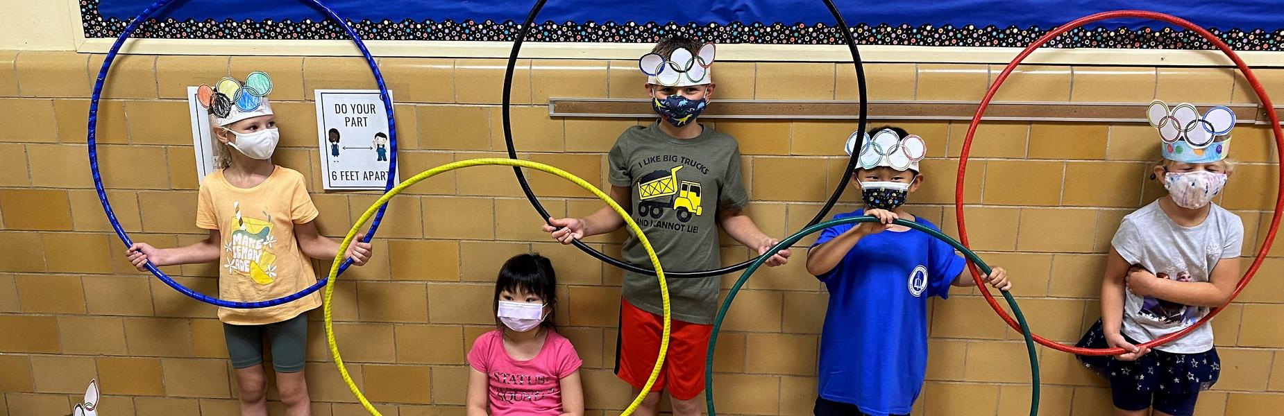 Photo of students posing with hula hoops to create Olympic rings
