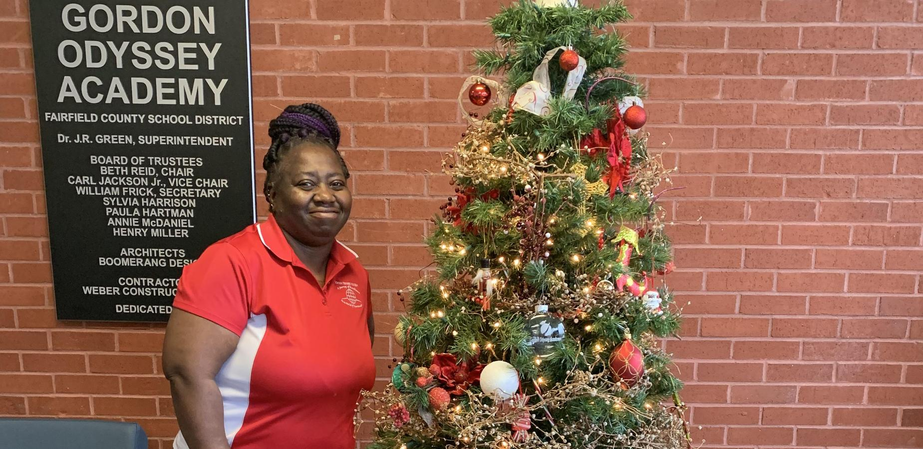 Mrs.Durham posing in front of the Christmas tree