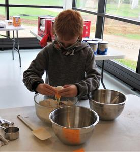 A student carefully cracks an egg into the cake batter.