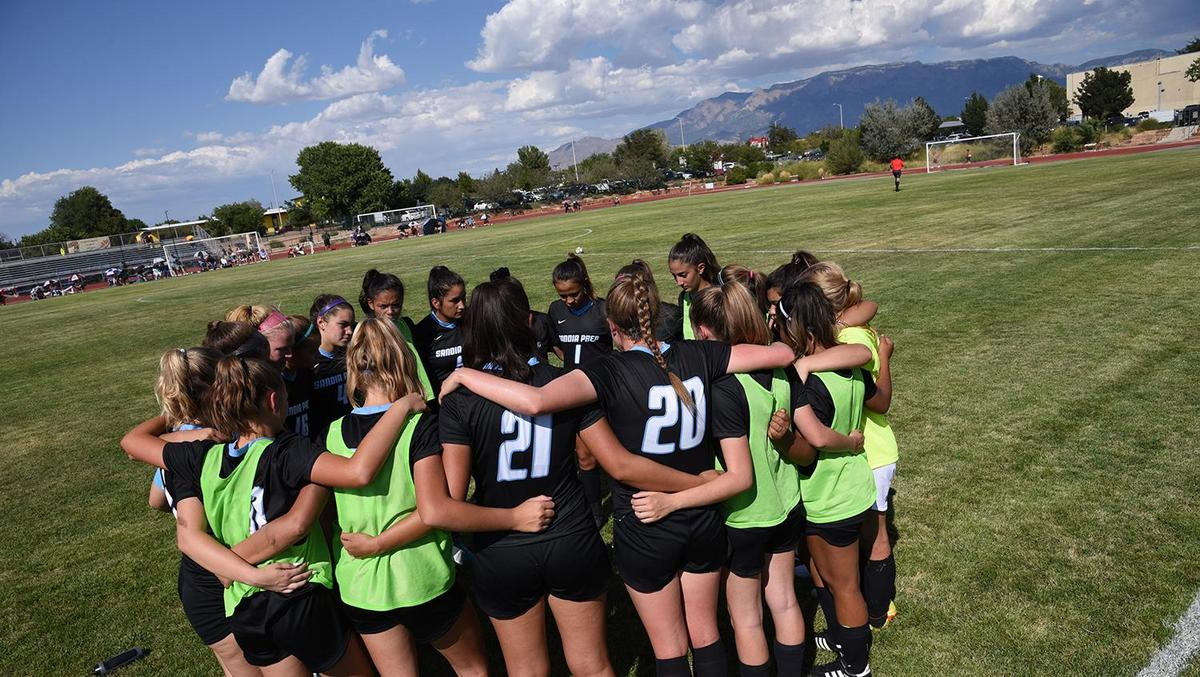 Girls Soccer Huddle with Sandia Mountains in the background