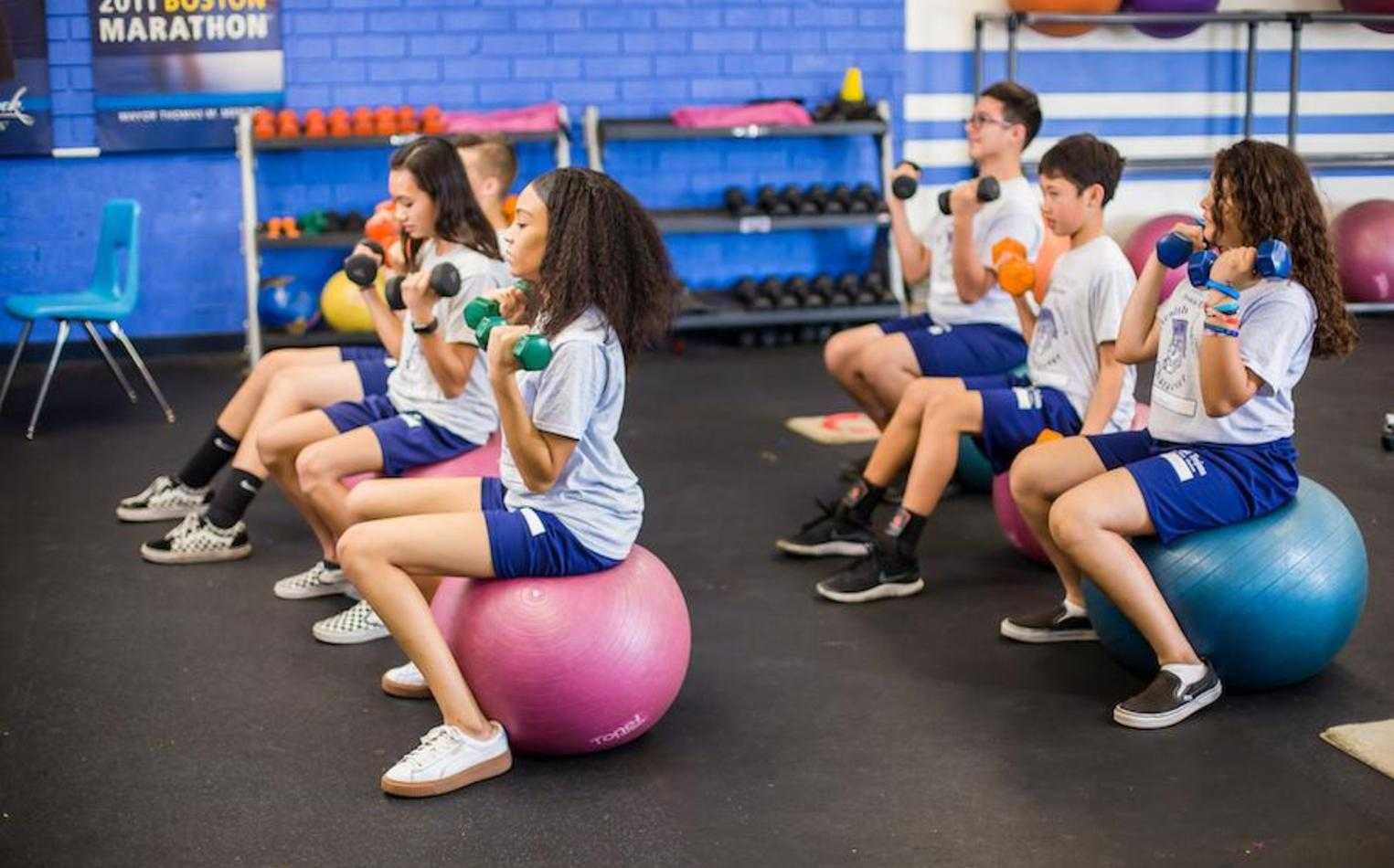 Middle school students working out in gym class.