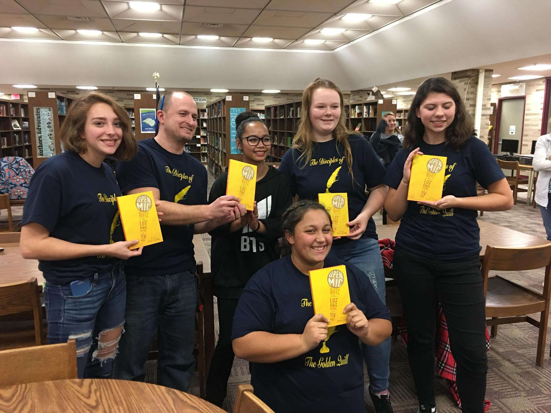 Group of students wearing matching shirts holding up copies of a book