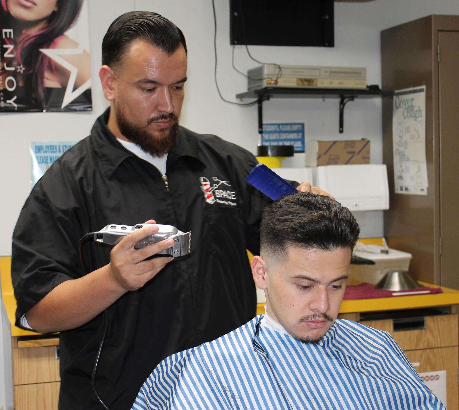 Barbering student giving hair cut
