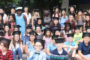 Fifth grade class poses with bear statue