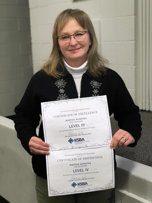 Martha Wynstra holds certificates awarded by KSBA.