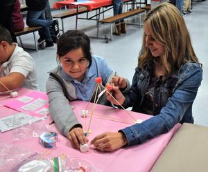 Foster Elementary School students and their parents work together to launch candies from a catapult during the school's annual science, technology, engineering, arts and mathematics (STEAM) night on Jan. 31.