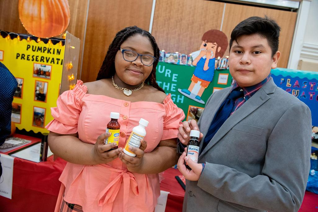 Two students holding small bottles of medicine