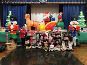 pre-k class posing with their gifts and santa, teachers, aides