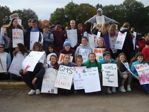 photo of 20 students outside with signs against hunger