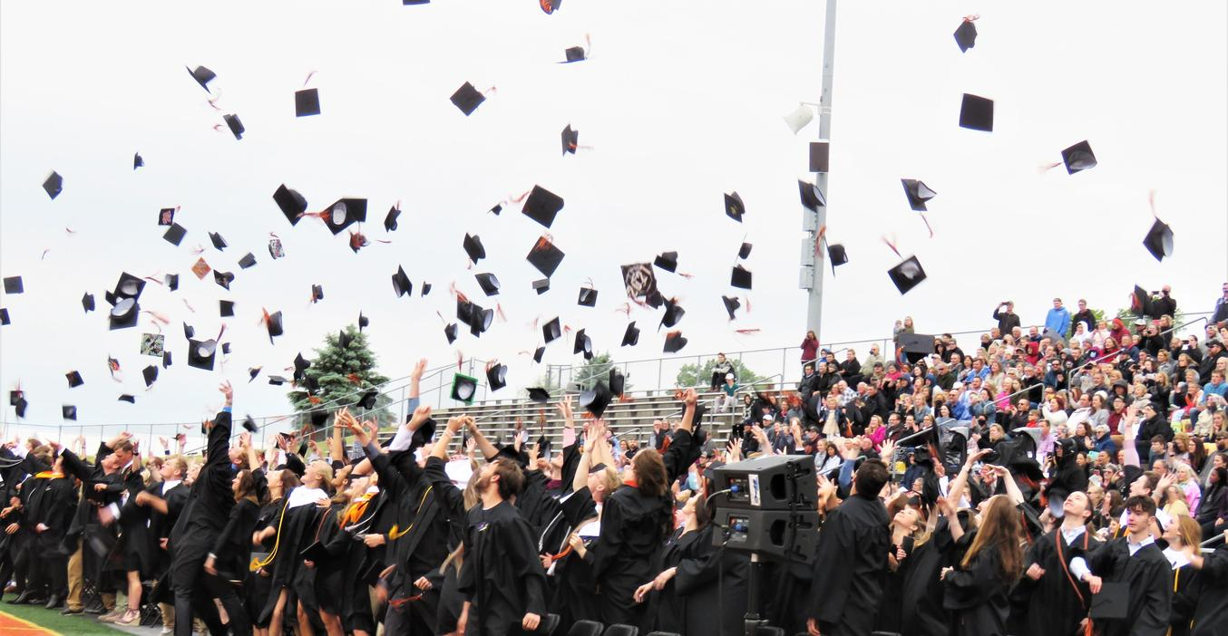 Graduation caps fly in the air at the end of the ceremony.
