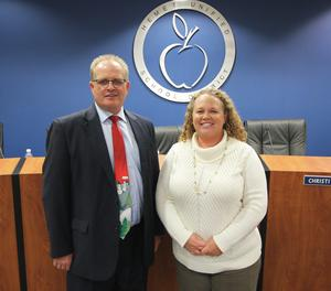 Rob Davis and Megan Haley smiling in front of the HUSD logo in the board room.