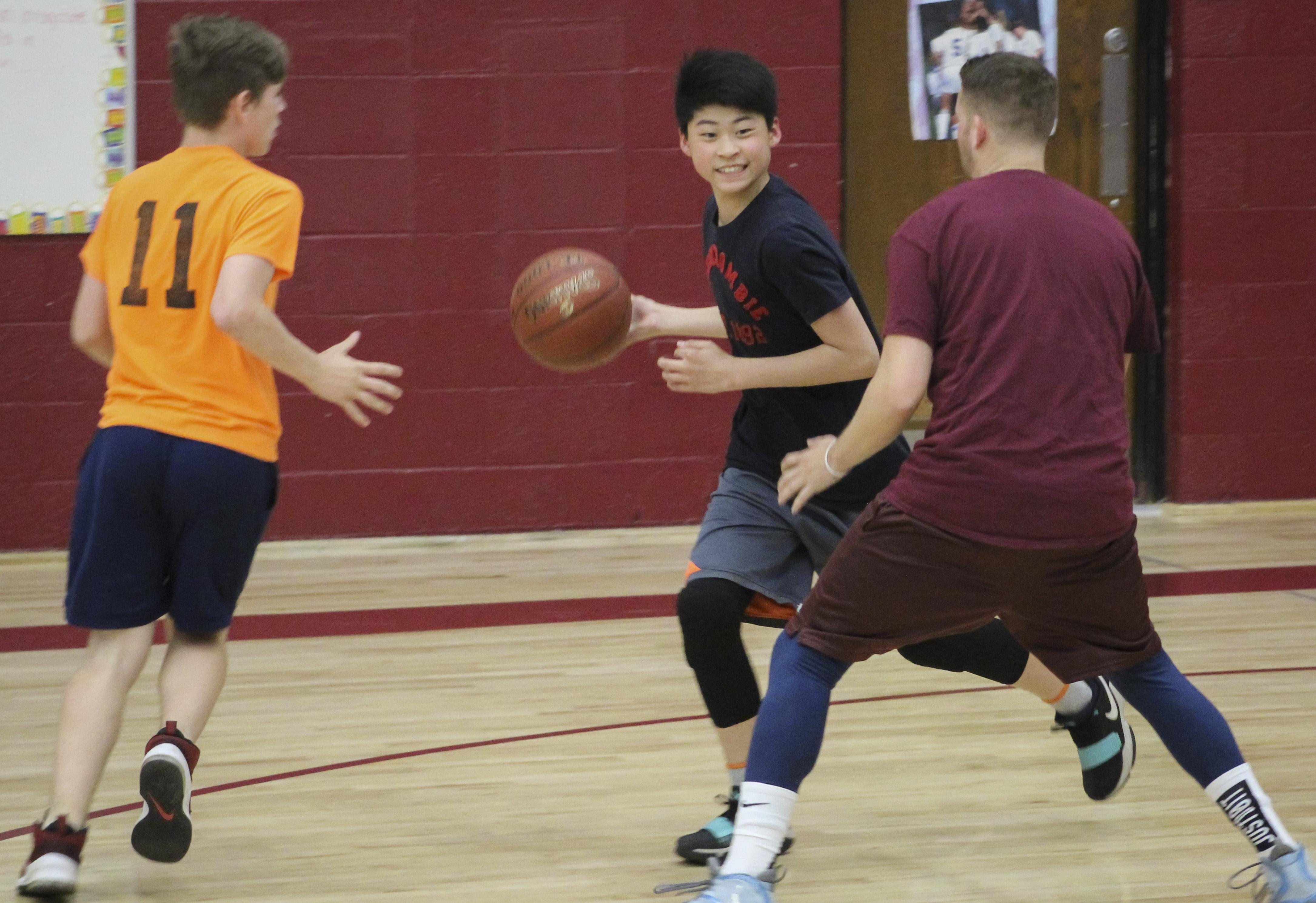 Two students and a teacher playing basketball