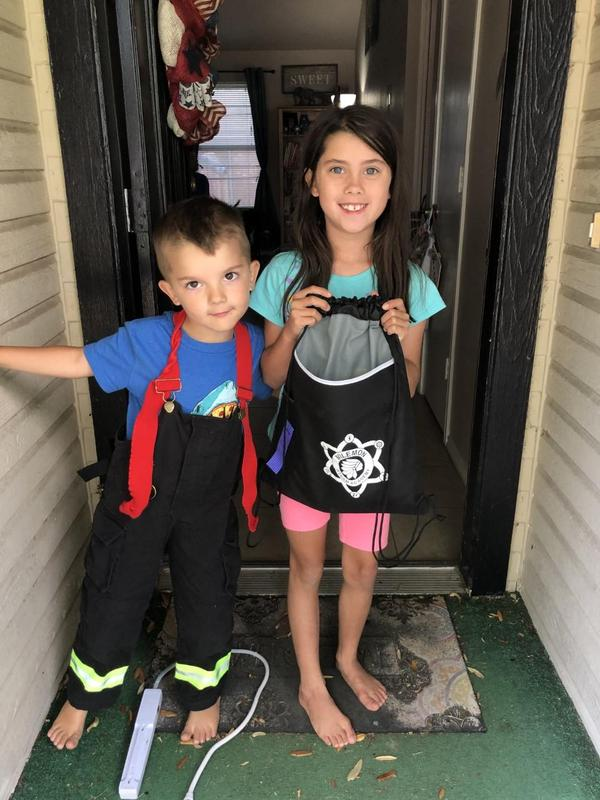 boy and girl holding bags of goodies outside their home