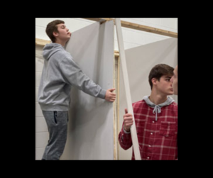 two boys hang drywall in class