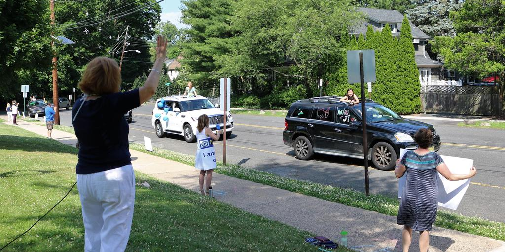 Photo of Franklin principal and staff cheering on 5th graders as they pass by in Grade 5 Clap Out Car Parade.