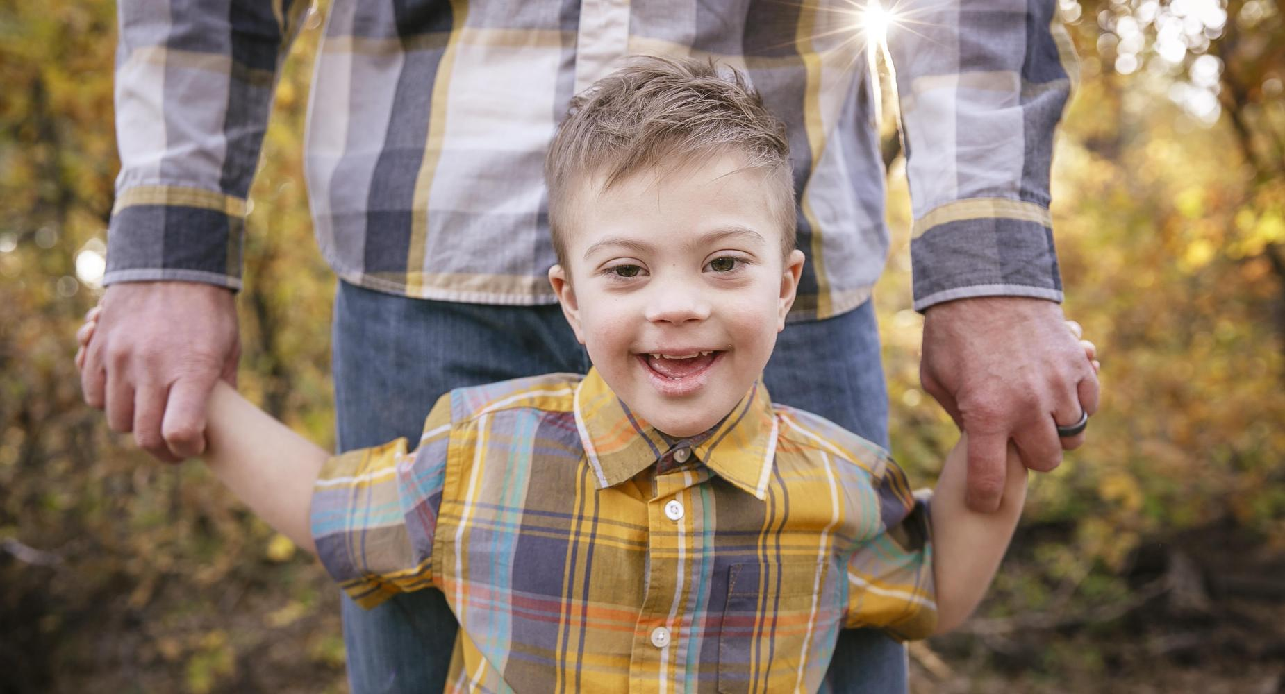 a smiling boy with down syndrome holding hands with his father.  Both are wearing matching flannel shirts