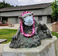 cougar statue in quad with mask and grad Lei