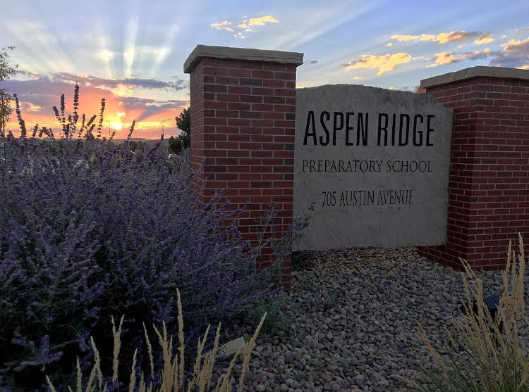 The glorious sunrays cascade over the stone sign welcoming people to Aspen Ridge