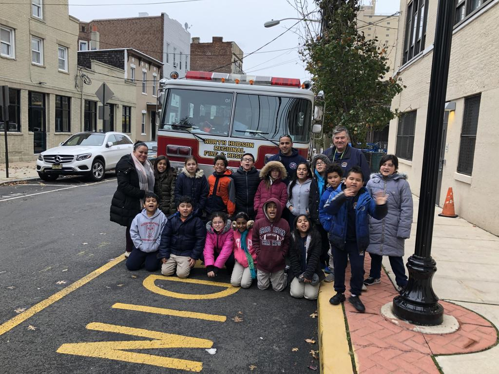 North Hudson Firefighter with a another class of students and their teacher in front of the fire engine in the front of the school