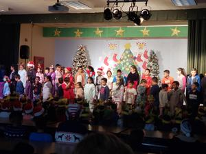 Students performing a Christmas song on stage.