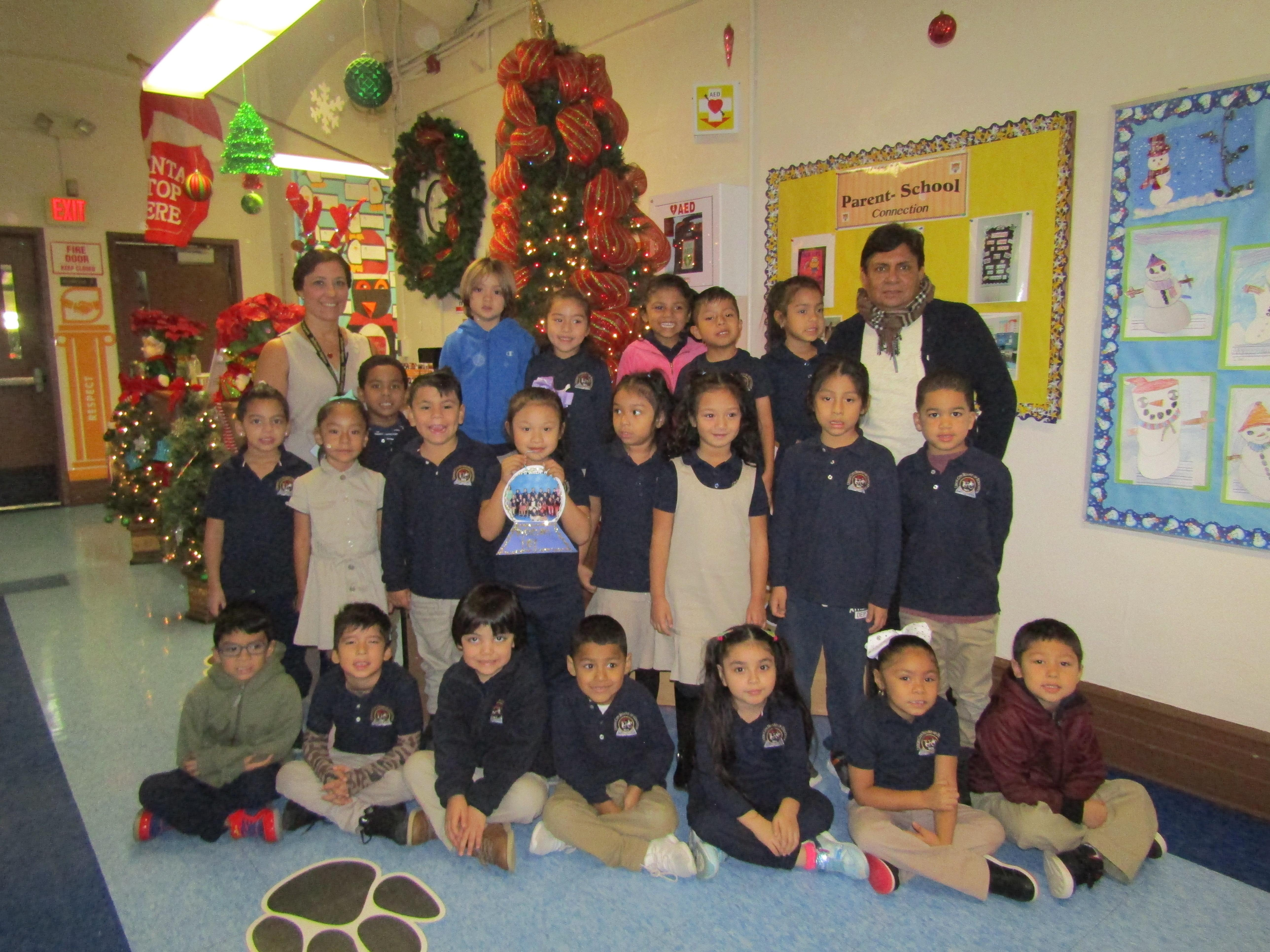 Kindergarten with teacher and aide in front of Christmas Tree
