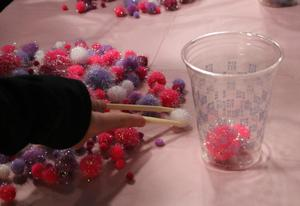 Closeup photo of Tamaques student's hand as he tries to pick up a small fuzzy ball with chopsticks during a Valentine's Day activity.