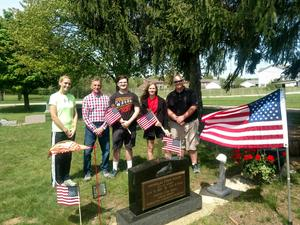 TKMS 8th graders and teachers pause at the grave of Cpl. Nicholas Roush as they decorate the cemeties with flags.
