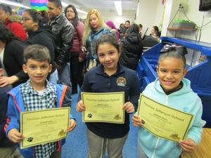 three kids proudly showing off their honor certificates